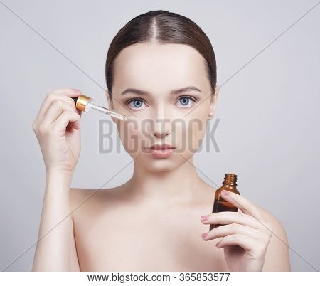 Close Up Of Model Brunette Girl With Cosmetic Oil On Her Face With Pipette. Beauty Therapy Concept.