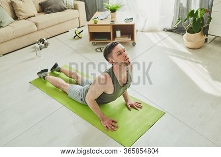 Active athlete in sportswear bending backwards while lying on mat on the floor of living-room and training in home environment