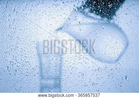 Pitcher with drinking water and a glass with a drink behind a glass with drops of water