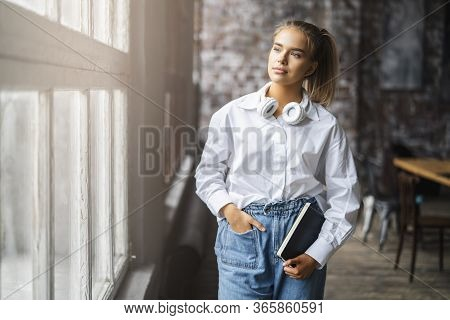 Beautiful Blonde Girl Holding Smartphone And Notebook In Her Hands. Business Woman Uses Mobile Phone