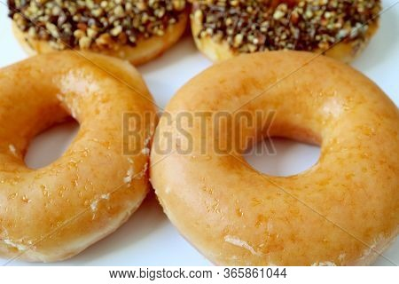 Closeup Delectable Sugar-glazed Donuts With Blurry Another Glazed Donuts In Background
