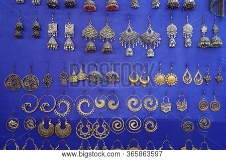 Colorful Handmade Earrings Hanging In Blue Background For Sale For Tourists At The Street Market In