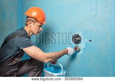 The Worker Is Applying Waterproofing Paint To The Wall In The Bathroom.