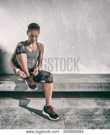 Exercise active Asian woman getting ready for run tying running shoes on gym bench at home wearing smartwatch technology. Athlete sporty runner in activewear living a healthy lifestyle.