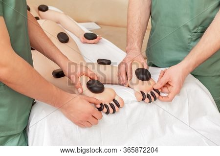 Female Receiving Hot Stones Massage On Feet, Toes And Legs In Four Hands.