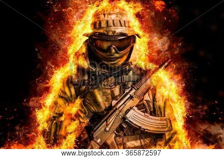 Special Forces Soldier In Fire With Assault Rifle And Handgun. Isolated On Black Background
