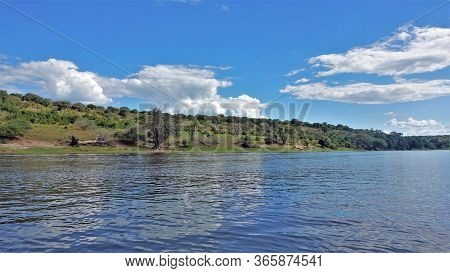 Botswana. Calm River. Clouds Are Reflected In Blue Water. On The Shore Of Green Grass, Trees. Silenc