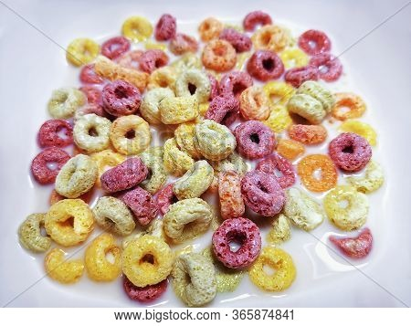 Colorful Ring-shape Fruity Cereal With Milk In White Bowl