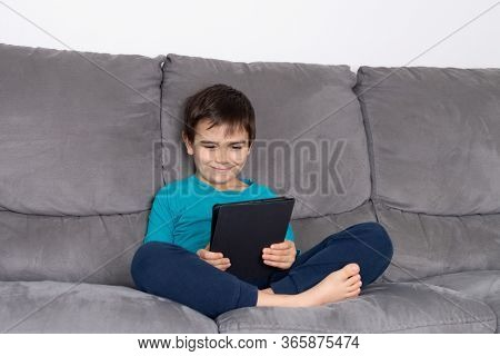 Boy With Tablet Pc Sitting On Sofa, Kids Using Technology, Home School Education, Boy Happy To Stay