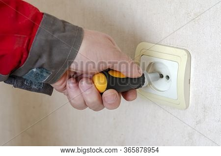 Hand Man In Working Clothes Twists Screwdriver Mounting Screw From The Outlet In The Wall.