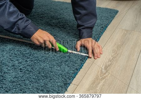 Worker Using Cutter While Installing New Carpet Flooring In Room. Carpet Restoration, Carpet Trimmin