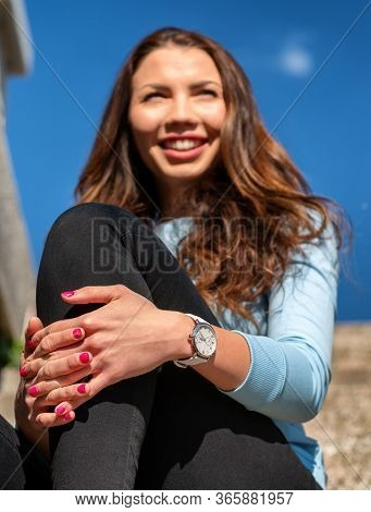 Happy Smiling Girl With Wristwatch Sitting Outside With Clapsed Hand. Focus On Hands