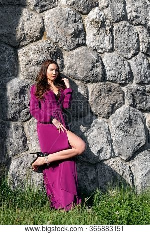 Attractive Asian Woman In High Heels Posing With Luxury Violet Long Dress
