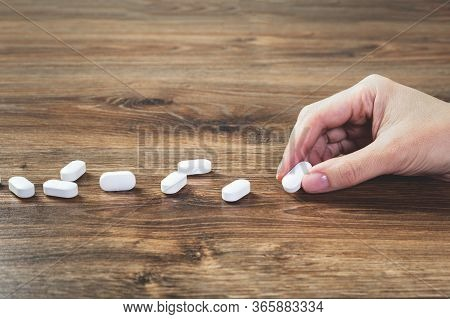 Hand With White Tablets Pills Lined On Wooden Table. Pharmacy. Healthcare And Medicine Concept Drugs