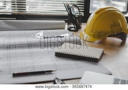 Construction Working Tool, Blueprint And Yellow Safety Helmet On Architect Workplace Desk In Meeting