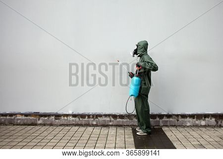 Disinfection Of The City From Coronavirus, A Man In A Protective Suit And A Respirator Against The B