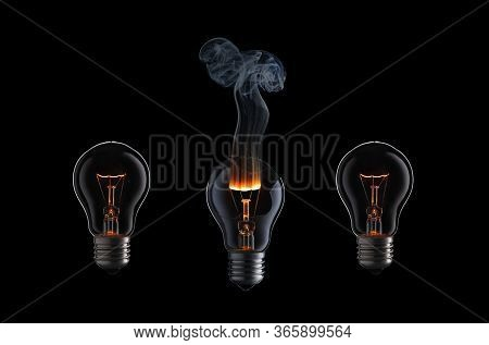 Light Bulb With Fire And Smoke On Black Background.