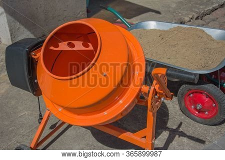 Cement Mixer Machine Is At Construction Site With Wheelbarrow, Tools, Sand And Cement Bag. Orange Co