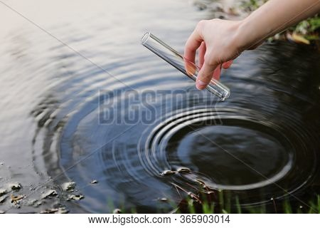 Scientist And Biologist Hydro-biologist Takes Water Samples For Analysis. Hand Is Collects Water In