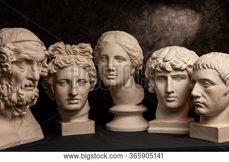 Group Gypsum Busts Of Ancient Statues Human Heads For Artists On A Dark Background. Plaster Sculptur