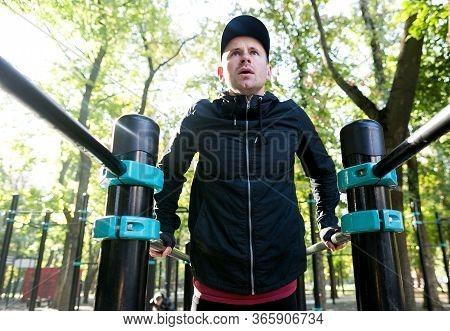 Focused Sportsman Exercising On Parallel Bars. From Below Of Man In Black Sportswear