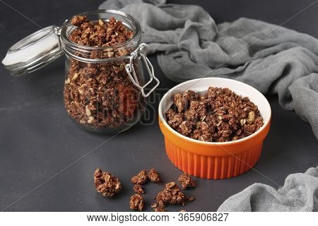Granola Crispy Muesli With Natural Honey, Chocolate, Nuts In A Bowl And Glass Jar Against A Dark Bac