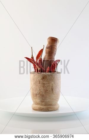 Red Chillies With Mortar And Pestle On White Background.