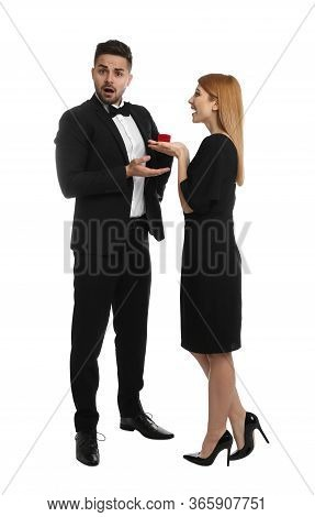 Young Woman With Engagement Ring Making Marriage Proposal To Her Boyfriend On White Background
