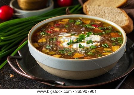 Traditional Dish Russian Cuisine. Cold Summer Okroshka Soup Close-up With Kvass, Sausage And Vegetab