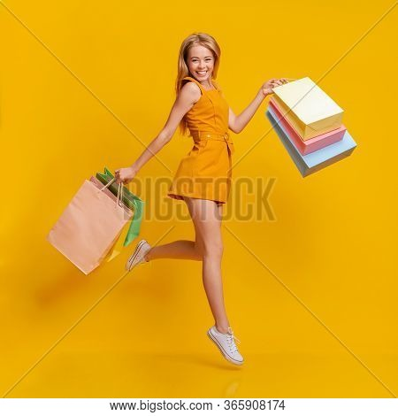 Seasonal Sales. Beautiful Shopaholic Young Girl Jumping In Air With Lots Of Shopping Bags In Hands O