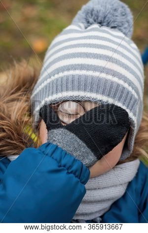 Little Funny Boy In Round Glasses And Winter Clothes - Hat, Scarf And Jacket With Fur - Makes A Face