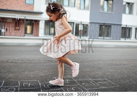 Horizontal Image Of Little Girl Playing Hopscotch On Playground Outdoors. Cute Child Plays Next To T
