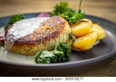 Cooked Cod Fish Cutlet With Potatoes, Lettuce Cabbage, Cooked Roots And Sour Cream Sauce