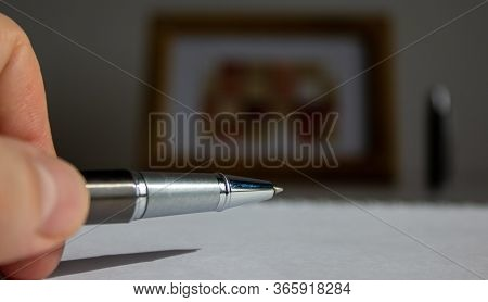 Pen On Beautiful White Fon On Warm Light. Wooden Picture Frame And Cap In The Background.