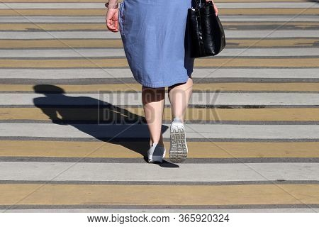 Woman In A Summer Dress Walking On Pedestrian Crossing, Street Safety Concept. Female Legs On The Cr