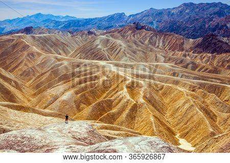 Tourist with a camera is looking for a beautiful landscape. Zabriskie Point, Death Valley in California, USA. Magnificent erosion landscape. Sunset. The concept of active, extreme and photo tourism