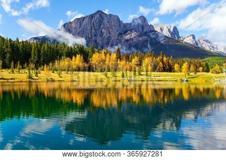 The Canadian Rockies. Bright autumn forest is reflected in the smooth water of the lake. The city of Canmore is  in Canadian Banff National Park. The concept of active, ecological and photo tourism
