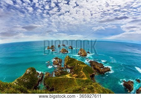 New Zealand. The picturesque coast of the Pacific Ocean near Nugget Points. Big stones - rocks along the shore. Photo taken by Fish Eye lens. The concept of active, environmental and photo tourism