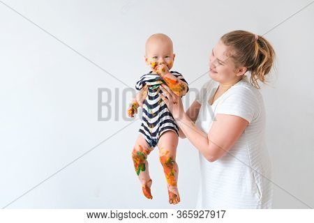 Mother Holds Cheerful Grimy Dirty Baby Playing With Paint Over White Wall Background. Happy Leasure