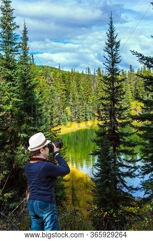 Middle-aged woman in a beautiful hat takes pictures of the lake. Northern Cordillera. Cold cloudy autumn day. The Northern Rocky Mountains. The concept of ecological, active and photo tourism