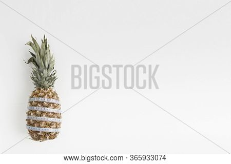 Pineapple Fruit With A Centimeter Measuring Tape. On White Background. Healthy Food. Food For Weight