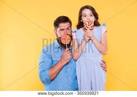 Get Day Like Candy. Father And Child Cover Mouth With Candy Yellow Background. Candy Shop. Lollipop