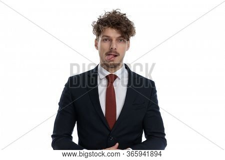 Funny businessman making a clumsy face and sticking out his tongue while wearing suit and standing on white studio background