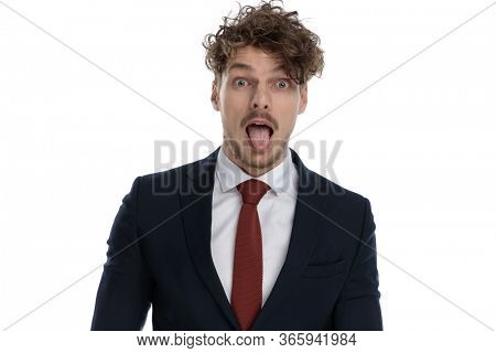 Funny businessman sticking out his tongue and making silly face while wearing suit and standing on white studio background