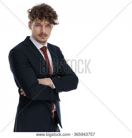 Tough businessman looking forward with his arms folded while wearing suit and standing on white studio background