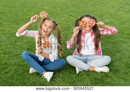 Sweet Childhood. Happy Children Hold Candy Sit Green Grass. Candy Shop. Lollipop Treats. Candy Synon