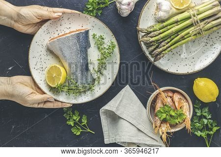 Woman Holds Ceramic Plate With Raw Trout Fish, Thyme And Lemon In Hands On Black Concrete Table Surf