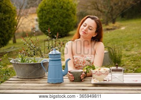 Concept Of Breakfast And Teatime In Open Air. Girl Drinks Tea From Vintage Teapot And Mug (inscripti