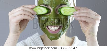Woman With A Towel On Her Head Makes A Cosmetic Face Mask Of Green Clay With Cucumbers. Funny Home S