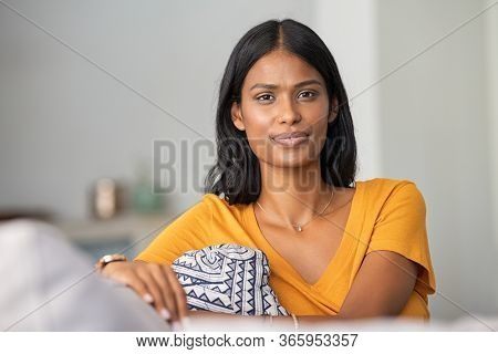 Confident indian woman relaxing on couch at home. Thoughtful smiling middle eastern girl sitting on sofa and looking at camera. Portrait of satisfied young woman daydreaming at home with copy space.